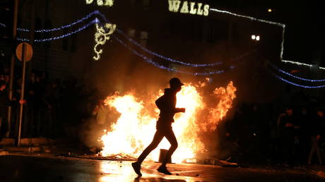 A Palestinian walks by a burning barricade during clashes between groups of rival demonstrators and security forces in Jerusalem, April 22, 2021.