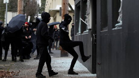 FILE PHOTO: Protesters smash windows at the Democratic Party of Oregon headquarters during a protest after the inauguration of President Joe Biden, in Portland, Oregon.