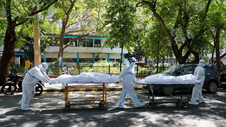 Health workers wearing personal protective equipment carry bodies of people outside a hospital in New Delhi, India on April 24, 2021.