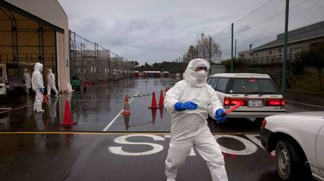 A man directs traffic at a vehicle near near Tokyo Electric Power Co. (TEPCO)'s tsunami-crippled Fukushima Daiichi Nuclear Power Plant in Fukushima (FILE PHOTO) © REUTERS/David Guttenfelder/Pool