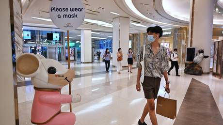 A shopper walks past a mouse statue in a mask in a shopping mall in Bangkok, Thailand on April 26, 2021. © Lillian Suwanrumpha / AFP