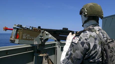 FILE PHOTO: A crew member aboard the Royal Australian Navy frigate HMAS Newcastle holds a gun during Australia's largest maritime exercise 'Exercise Kakadu' being conducted off the coast of Darwin in northern Australia, September 8, 2018