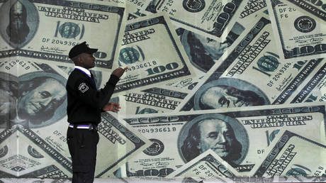 FILE PHOTO: A security guard walks past a montage of old US dollar bills outside a currency exchange