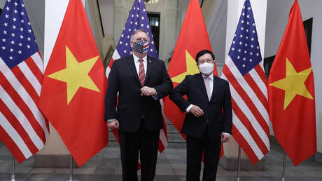 This picture taken and released on October 30, 2020 by the Vietnam News Agency shows Vietnam's Foreign Minister Pham Binh Minh (R) bumping elbows to greet US Secretary of State Mike Pompeo before a meeting in Hanoi.