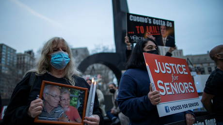People hold a vigil honoring those that have died of Covid-19 in nursing homes one year after the March 25, 2020 executive order by Governor Andrew Cuomo in which nursing homes in New York state were forced to take in untested patients.
