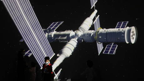 A child stands near a giant screen showing the images of the Tianhe space station at an exhibition featuring the development of China's space exploration, April 24, 2021