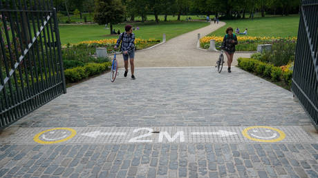 People push their bicycles towards a sign indicating social distancing of 2 metres is required in a park following the outbreak of the coronavirus disease (COVID-19), in Dublin, Ireland, May 8, 2020.