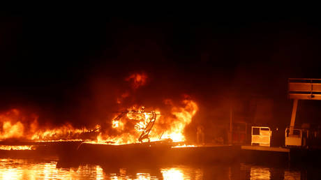 Boats engulfed in flames are seen at a dock near Markley Cove Resort during the LNU Lighting Complex Fire on the outskirts of Napa, California, U.S., August 19, 2020.