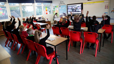 Children wave to friends from separate classes during an online assembly, as normal assemblies will not take place at the moment, on their first day of school at Holne Chase Primary School, amid the outbreak of the coronavirus disease (COVID-19), in Milton Keynes, Britain, September 3, 2020.