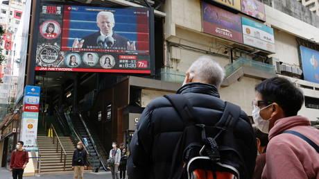 FILE PHOTO: People look at a TV screen showing news of US President Joe Biden after his inauguration, in Hong Kong, China January 21, 2021
