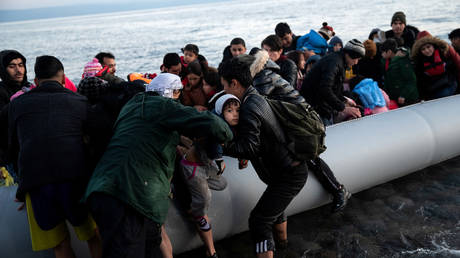 Migrants from Afghanistan arrive on a dinghy on a beach near the village of Skala Sikamias, Lesbos, Greece