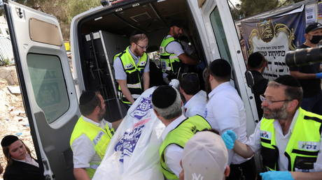 Rescue workers load a body into an ambulance on Mount Meron, northern Israel, after dozens were killed in a stampede at a religious event, April 30, 2021. © Ronen Zvulun / Reuters