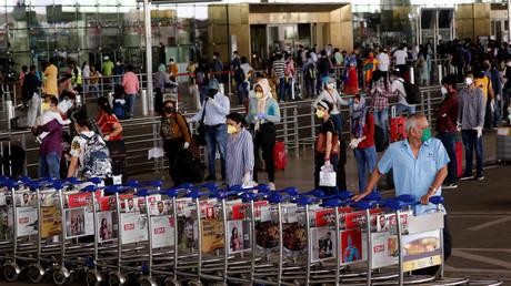 An airport staff member pushes trollies at the entrance of Chatrapati Shivaji International Airport in Mumbai, India, May 25, 2020 © Reuters / Francis Mascarenhas