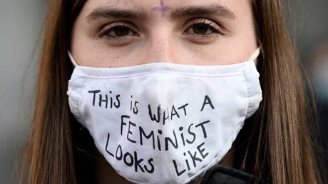 """A woman wears a protective face mask reading """"This is what a Feminist look like"""" during a demonstration"""