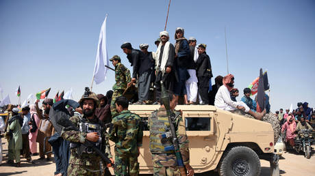 FILE PHOTO: Afghan Taliban militants and residents stand on a armoured Humvee vehicle of the Afghan National Army (ANA) as they celebrate a ceasefire, Kandahar, Afghanistan, June 17, 2018 © AFP / Javed Tanveer