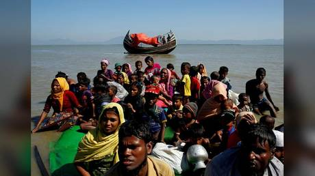 Rohingya refugees are shown sitting on a makeshift boat after crossing from Myanmar into Bangladesh in 2017.
