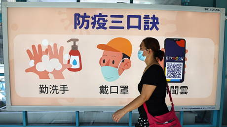 FILE PHOTO. A woman wears a face mask at a metro station in Taipei, Taiwan.
