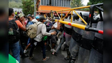 A caravan of Honduran migrants is shown in January trying to cross the border into Guatemala on their trek toward the US.