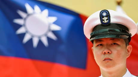 """A Taiwan Navy honor guard looks on in front of a Taiwan flag during the launch ceremony for Taiwan Navy's domestically built amphibious transport dock """"Yushan"""" in Kaohsiung, Taiwan (FILE PHOTO) © REUTERS/Ann Wang"""