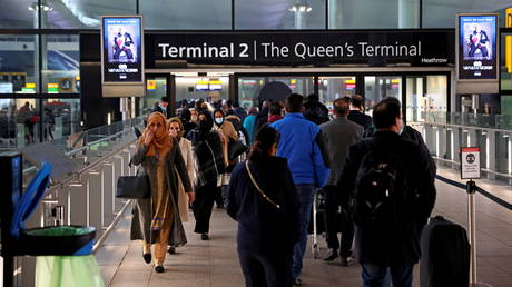 FILE PHOTO: People queue to enter terminal 2, as tighter rules for international travellers start, at Heathrow Airport.
