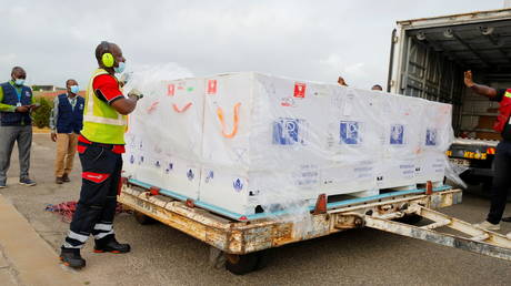 Workers load a truck with 350,000 doses of Oxford/AstraZeneca coronavirus disease (COVID-19) vaccines, redeployed from the Democratic Republic of Congo, at the Kotoka International Airport in Accra, Ghana. May 7, 2021.