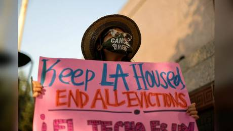 A protester is shown in Los Angeles last August opposing a wave of evictions. With home prices rising and Covid-19 lockdowns wiping out jobs, increasing numbers of Californians can no longer afford to live in the state.