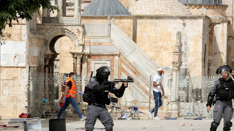 A member of Israeli police aims a weapon during clashes with Palestinians at the compound that houses Al-Aqsa Mosque, known to Muslims as Noble Sanctuary and to Jews as Temple Mount, in Jerusalem's Old City, May 10, 2021.