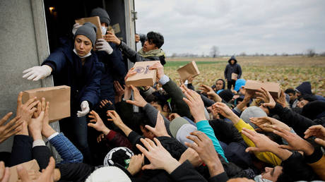 FILE PHOTO. Members of United Nations High Commissioner for Refugees deliver food to migrants at Turkey's Pazarkule border crossing with Greece's Kastanies, in Edirne, Turkey. © Reuters / Umit Bektas
