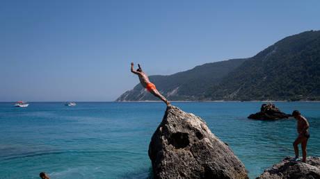 FILE PHOTO: A man dives at Agios Nikitas beach on the island of Lefkada, Greece. © Reuters/Dimitris Rapakousis