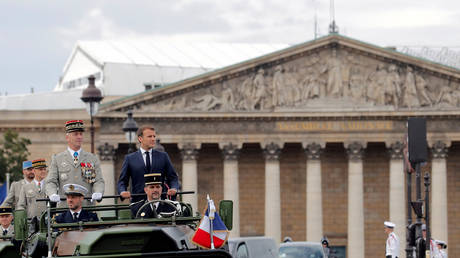 FILE PHOTO: France's President Emmanuel Macron and French Armies Chief Staff General Francois Lecointre stand in the command car as they review troops before the start of the Bastille Day military parade in Paris, France July 14, 2020