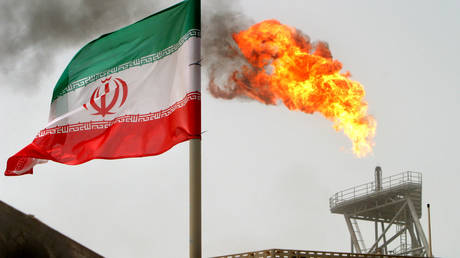 FILE PHOTO: A gas flare on an oil production platform is seen alongside an Iranian flag in the Persian Gulf