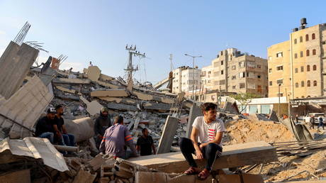 Palestinians sit on the ruins of a building that was destroyed by Israeli airstrikes in Gaza, May 13, 2021. © Mohammed Salem / Reuters