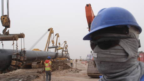 Workers set up a natural gas pipeline at Iraq's border with Iran in Basra, southeast of Baghdad.