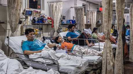 Patients who contracted the coronavirus lie in beds while connected to oxygen supplies inside the emergency ward of a Covid-19 hospital on May 03, 2021 in New Delhi, India.