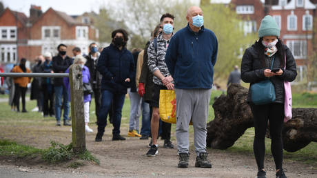 People stand in line for coronavirus surge testing on Clapham Common, south London.