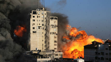 Smoke and flames rise from a tower building as it is destroyed by Israeli air strikes amid a flare-up of Israeli-Palestinian violence, in Gaza City