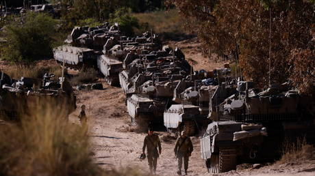 Israeli soldiers walk next to tanks near the border between Israel and the Gaza Strip
