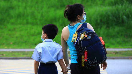 A woman walks a child to school donning the protective mask on June 8, 2020 in Singapore.