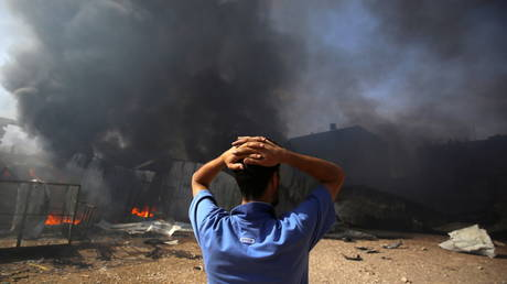 A man stands near a burning sponge factory in the northern Gaza Strip on May 17, 2021.