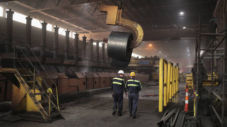 Workers remove a coil from the production line for quality-control testing during steel production at steel mill.