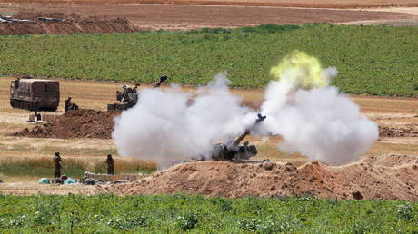 FILE PHOTO: An Israeli military artillery unit fires a shell, as seen from the Israeli side of the border with the Gaza Strip, May 16, 2021.