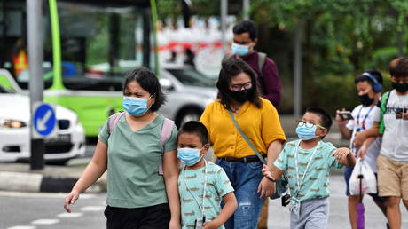 People wearing face masks cross a road amid the coronavirus disease outbreak in Singapore on May 14, 2021.