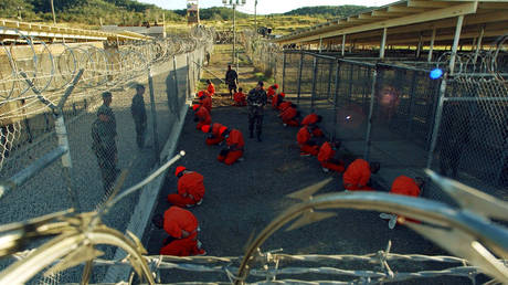 Detainees in orange jumpsuits sit in a holding area under the watchful eyes of Military Police at Camp X-Ray at Naval Base Guantanamo Bay, Cuba, during in-processing to the temporary detention facility on January 11, 2002.