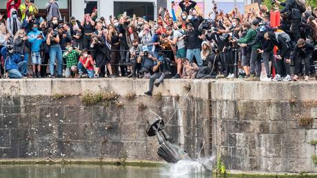 FILE PHOTO. The statue of 17th century slave trader Edward Colston falls into the water after protesters in Bristol, Britain