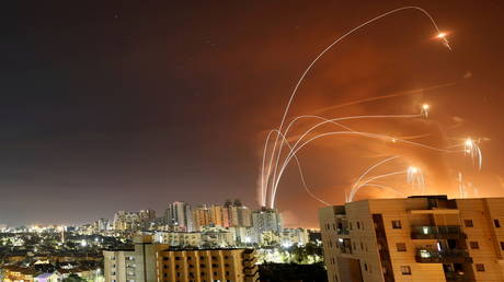 FILE PHOTO: Streaks of light are seen as Israel's Iron Dome anti-missile system intercepts rockets launched from the Gaza Strip, as seen from Ashkelon, Israel, May 12.
