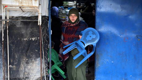 FILE PHOTO: A woman carries chairs out of a shop in al-Roj camp, Syria, January 10, 2020. © REUTERS/Goran Tomasevic