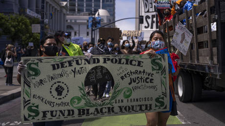 FILE PHOTO. Protesters march with a banner mocking a dollar bill that reads 'Defund police, Fund black youth' during a rally to mark Juneteenth in San Francisco, California. © AFP / VIVIAN LIN