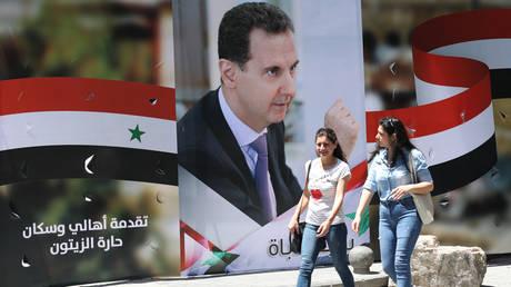 Syrian women walk past an election campaign billboard bearing a portrait of Syrian President Bashar al-Assad