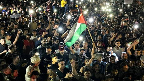 Palestinians celebrate in the streets following a ceasefire, in the southern Gaza Strip, May 21, 2021.