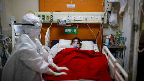 A medical worker takes care of a patient suffering from Covid-19, inside the Intensive Care Unit (ICU) ward at the Government Institute of Medical Sciences (GIMS) hospital, on the outskirts of New Delhi, India, May 21, 2021.
